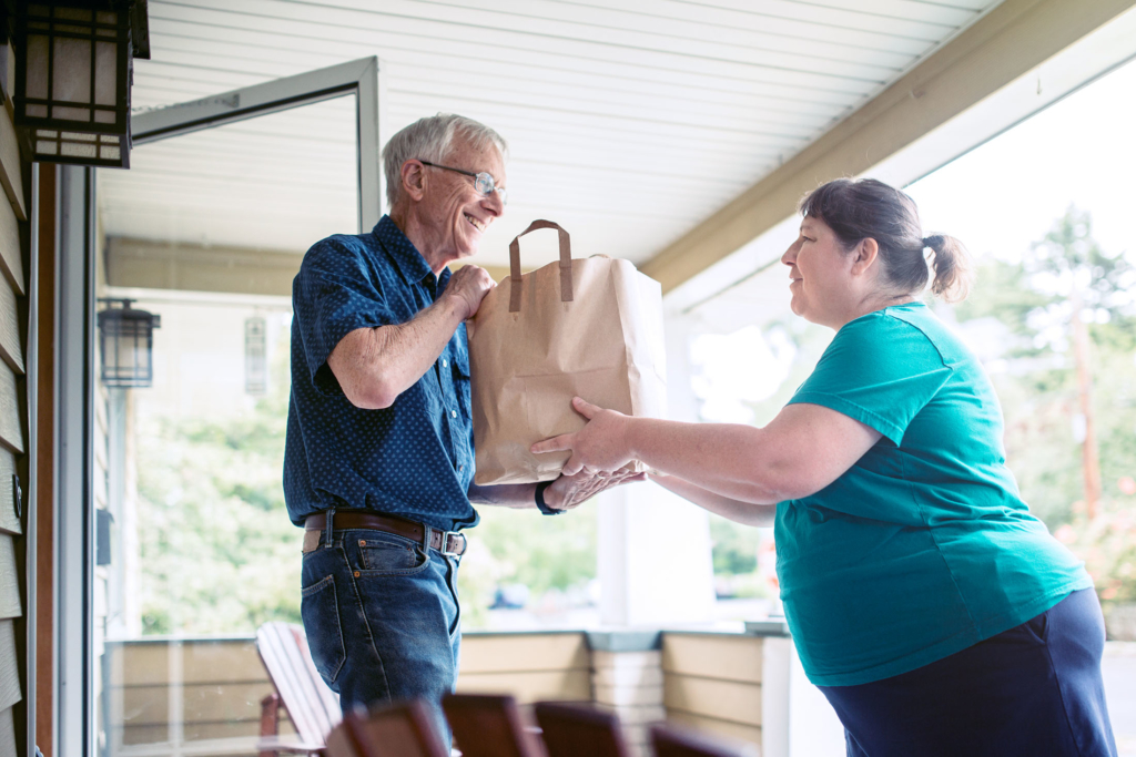 A kind and caring neighbor or friend delivers fresh produce from the grocery store to an elderly man at his home.  He receives the gift with a smile on his face, grateful for the help and assistance.  Horizontal image.